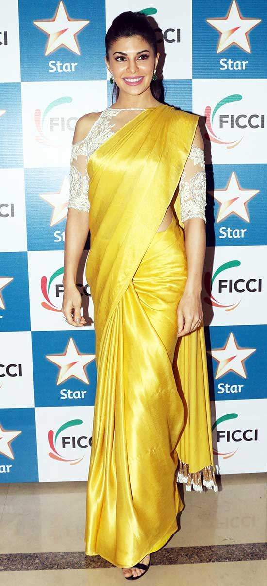 Jacqueline Fernandez In Gold Plain Saree-Paired With Cold Shoulder Blouse